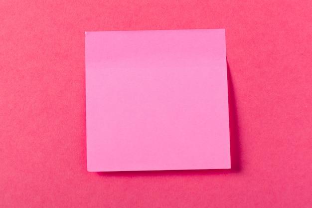 Leere papierstücke auf einem farbigen rosa hintergrund Premium Fotos