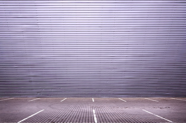 Leere parkplätze auf dem hintergrund einer metallwand mit platz für produktplatzierung Premium Fotos