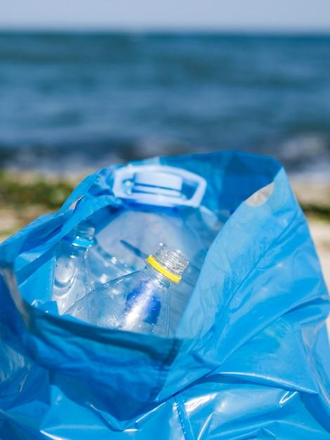 Leere plastikflasche in der blauen abfalltasche an draußen Kostenlose Fotos