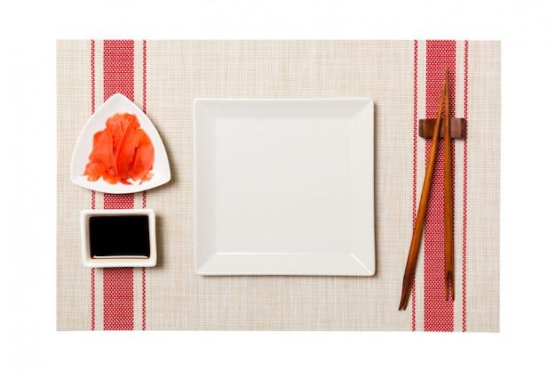 Leere platte des weißen quadrats mit essstäbchen für sushi und sojasoße, ingwer auf sushimattenhintergrund. Premium Fotos