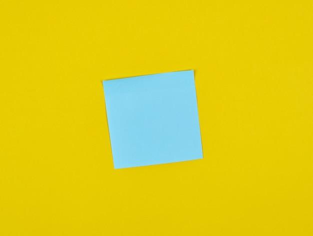 Leere quadratische aufkleber des blauen papiers auf gelb Premium Fotos