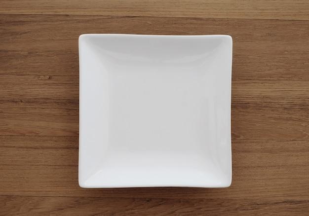 Leere quadratische weiße platte im hölzernen hintergrund Premium Fotos