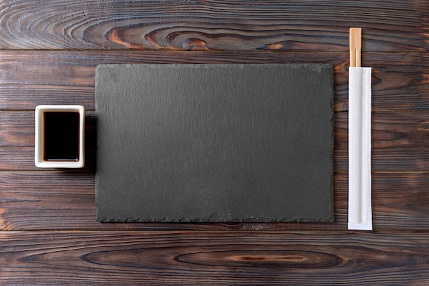 Leere rechteckige schwarze schieferplatte mit essstäbchen für sushi und sojasoße auf holz Premium Fotos