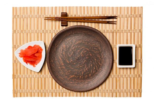 Leere runde braune platte mit essstäbchen für sushi und sojasoße Premium Fotos