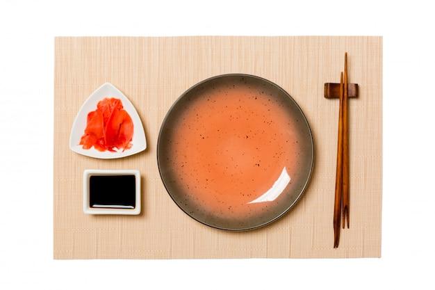 Leere runde braune platte mit essstäbchensushi, ingwer und sojasoße auf brauner sushimatte Premium Fotos