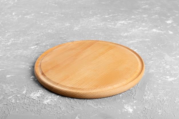Leere runde hölzerne platte auf strukturierter tabelle. hölzerne platte für das lebensmittel oder gemüse, die den kunden dienen Premium Fotos