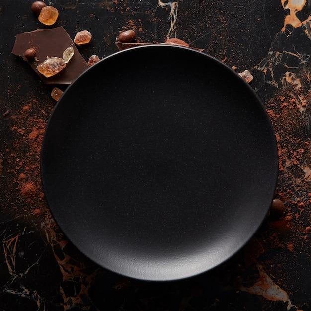 Leere schwarze platte auf dunkler marmoroberfläche. luftaufnahme mit kopierraum. Premium Fotos