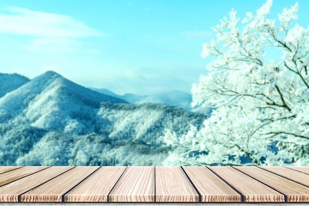 Leere spitzentabelle des hölzernen brettes vor unscharfem schneebergblick Premium Fotos