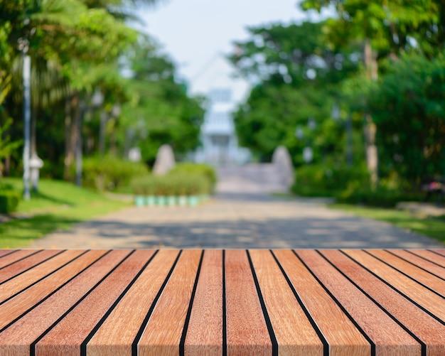 Leere tabelle des hölzernen brettes vor unscharfem hintergrund. braunes holz der perspektive mit unscharfen leuteaktivitäten im park - kann für anzeige verwendet werden oder ihre produkte zusammenbauen. frühling. weinlese gefiltertes bild. Kostenlose Fotos