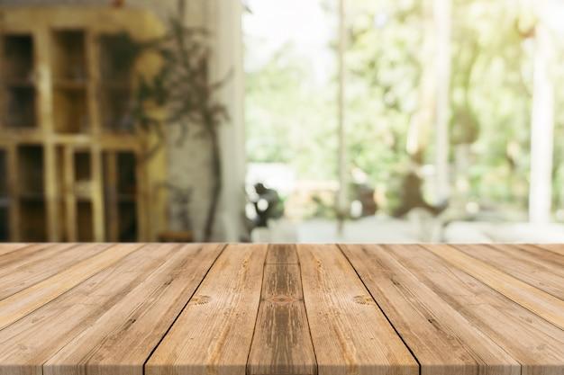 Leere tabelle des hölzernen brettes vor unscharfem hintergrund. braunes holz der perspektive über unschärfe in der kaffeestube - kann für anzeige verwendet werden oder ihre produkte zusammenbauen. spannen sie oben für anzeige des produktes an. Kostenlose Fotos