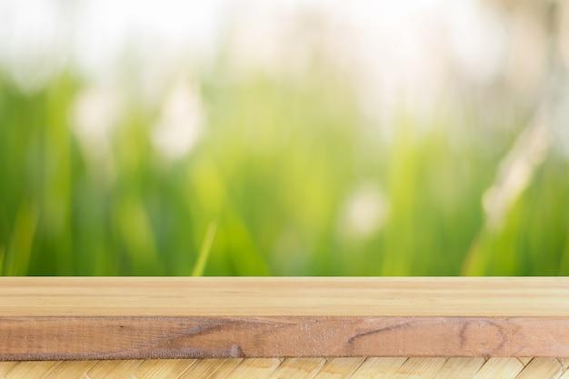 Leere tabelle des hölzernen brettes vor unscharfem hintergrund. braunes holz der perspektive über unschärfebäumen im wald - kann spott oben für anzeige benutzt werden oder ihre produkte zusammenbauen. frühling. jahrgang gefiltert. Kostenlose Fotos