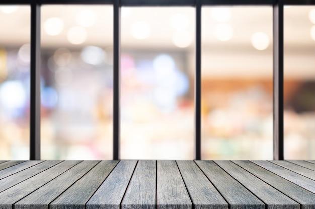 Leere tabelle des perspektivenholzbrettes auf die oberseite über unscharfem kaffeestubehintergrund Premium Fotos