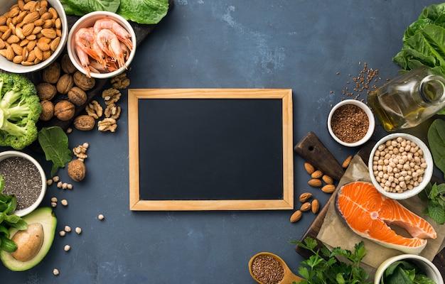 Leere tafel für ihren text mit nahrungsquellen für omega-3-fettsäuren und gesunde fette. lebensmittel mit hohem fettsäuregehalt, einschließlich gemüse, meeresfrüchten, nüssen und samen Premium Fotos