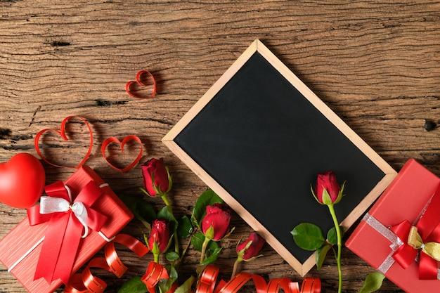 Leere tafel mit roten rosen und herzband auf altem holz Premium Fotos