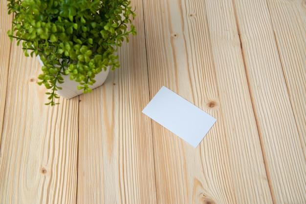 Leere visitenkarten und kleiner dekorativer baum im weißen vase auf hölzernem arbeitstisch Premium Fotos