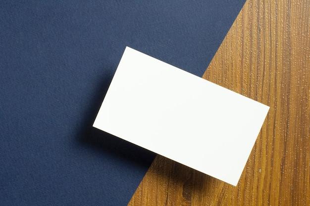 Leere visitenkarten zur hälfte liegen auf blau strukturiertem papier und holzschreibtisch Kostenlose Fotos