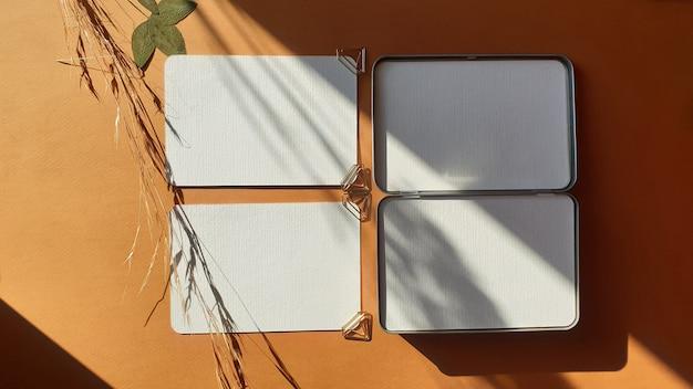 Leere weiße hochzeits-gruß-einladungskartenmodelle mit getrockneten blättern von pflanzen und von kräutern auf strukturiertem terrakottatabelle backgound. elegante moderne vorlage für die markenidentität. flachgelegt, draufsicht Premium Fotos