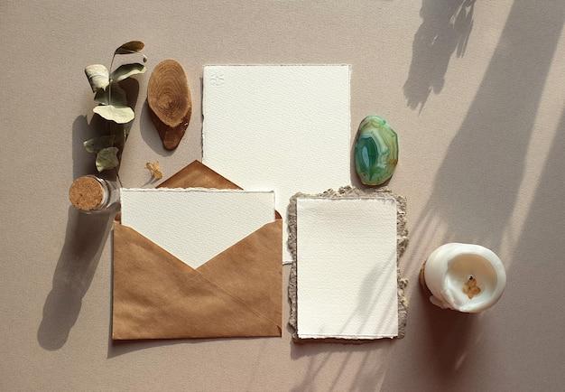 Leere weiße hochzeits-gruß-einladungskartenmodelle mit handwerksumschlag, getrockneter eukalyptus verlässt auf strukturiertem tabelle backgound. elegante moderne vorlage für die markenidentität. flachgelegt, draufsicht Premium Fotos