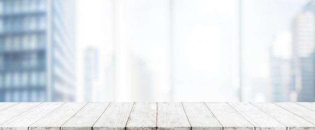 Leere weiße hölzerne tischplatte und unschärfeglasfensterwand-gebäudefahne verspotten herauf hintergrund Premium Fotos