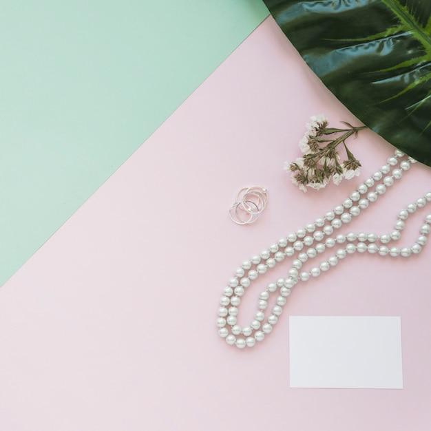 Leere weiße karte mit perlenhalskette, -blume und -blatt auf hintergrund Kostenlose Fotos