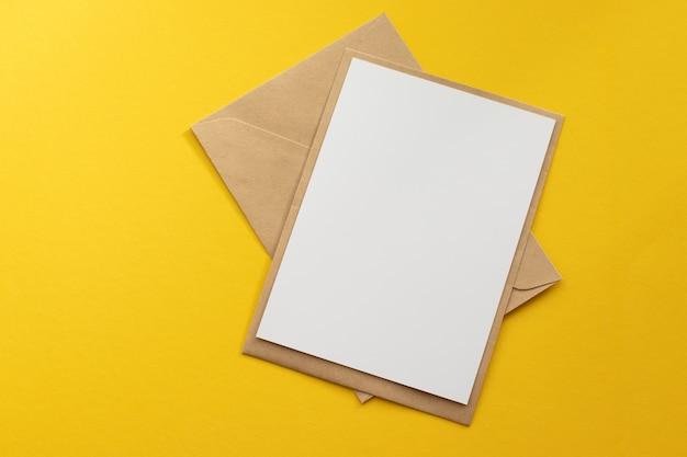 Leere weiße karte mit umschlagschablonenspott des braunen papiers des kraftpapiers oben auf gelbem hintergrund Premium Fotos