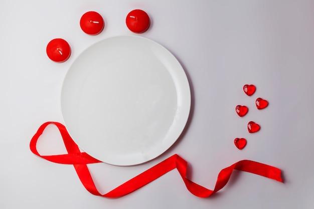 Leere weiße platte auf dem tisch mit rotem band, herzen und kerzen. Premium Fotos