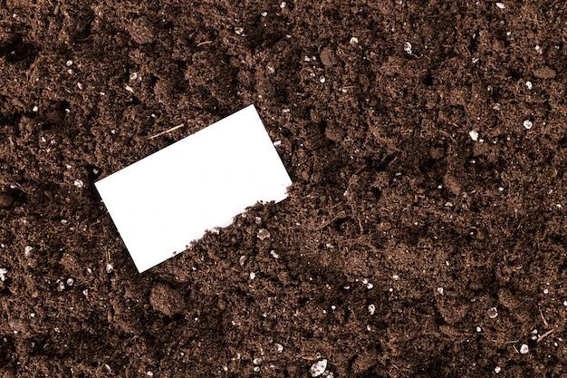 Leere weiße visitenkarte auf einem bodengrundkompost Premium Fotos