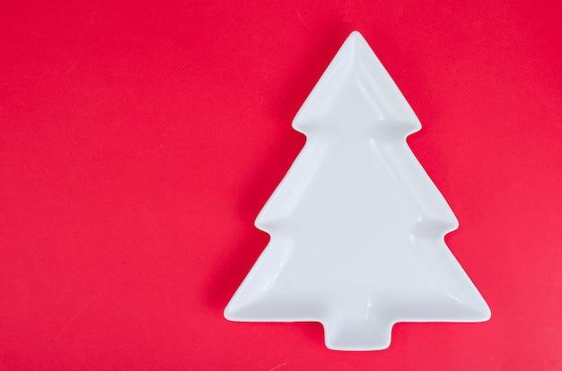 Leere weiße weihnachtsbaumplatte für tabellenweihnachtsfestliche einstellung. Premium Fotos