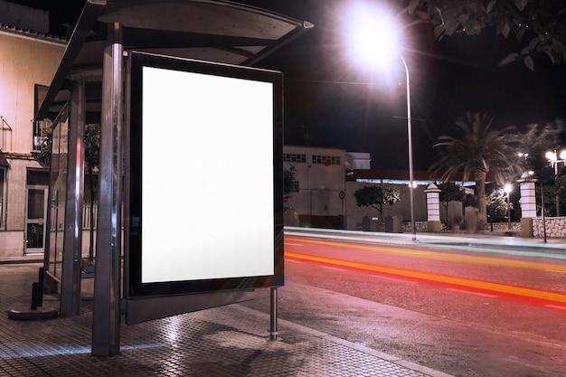 Leere werbung am wartehäuschen mit unscharfen ampeln nachts Kostenlose Fotos