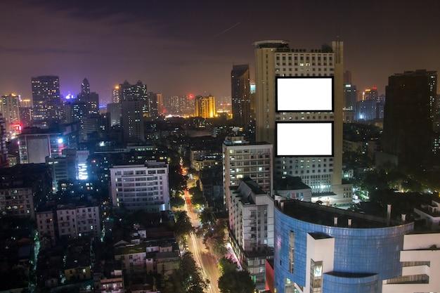 Leere werbungsanschlagtafel auf dem hohen gebäude, stadtlandschaft, textnachricht für werbung Premium Fotos