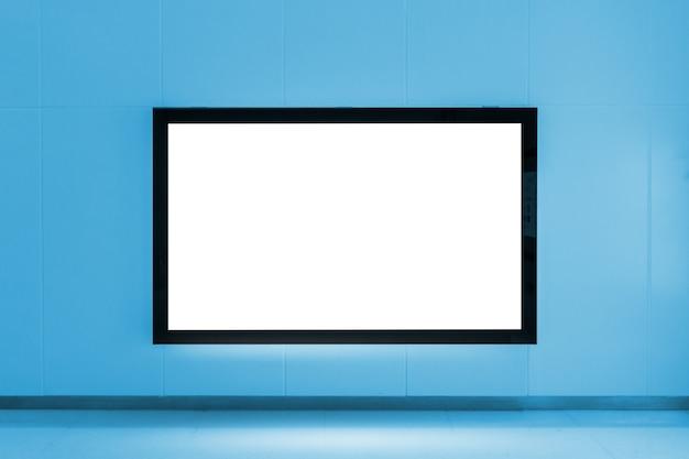 Leere werbungsanschlagtafel auf der wand an der u-bahn-bahnstation auf blauem farbton Premium Fotos