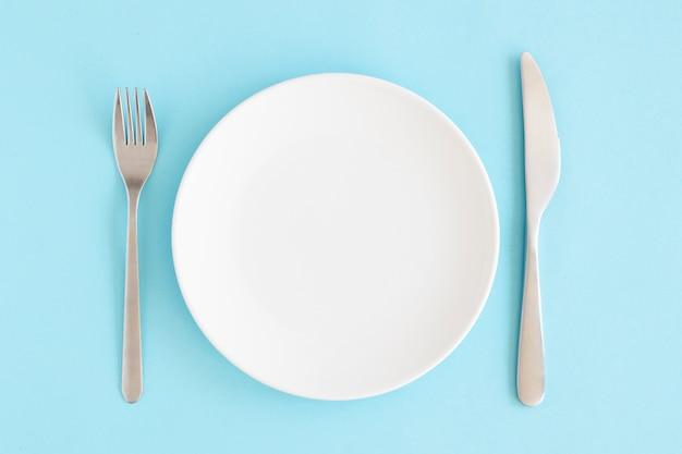 Leeren sie weiße platte mit gabel- und buttermesser über blauem hintergrund Kostenlose Fotos