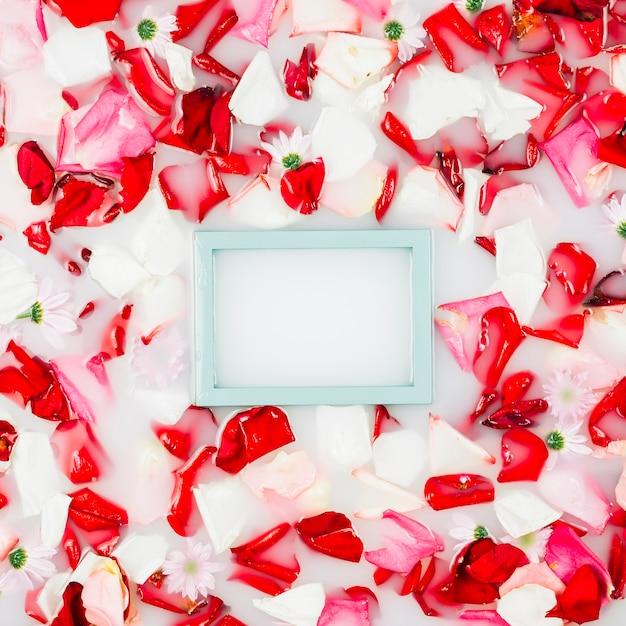 Leerer bilderrahmen mit den blumenblumenblättern, die auf wasser schwimmen Kostenlose Fotos