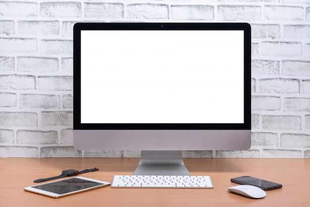 Leerer bildschirm von allen in einem computer mit tablette, intelligentem telefon und intelligenter uhr auf holztisch, weißer backsteinmauerhintergrund Premium Fotos
