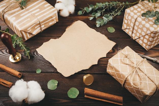 Leerer buchstabe mit einer feder auf dem alten hölzernen hintergrund verziert mit weihnachtsgegenständen Premium Fotos