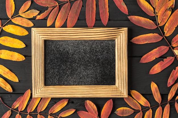 Leerer fotorahmen und bunter herbstlaub auf schwarzem Premium Fotos