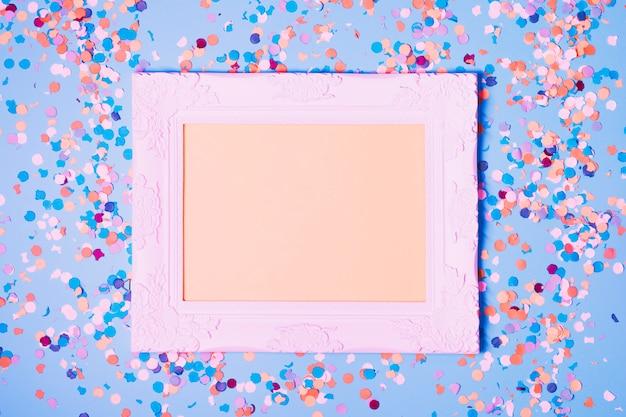 Leerer fotorahmen und dekorative konfettis auf blauem hintergrund Kostenlose Fotos