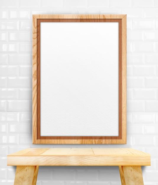 Leerer hölzerner fotorahmen, der an der weißen fliesenwand auf hölzerner tabelle hängt. Premium Fotos