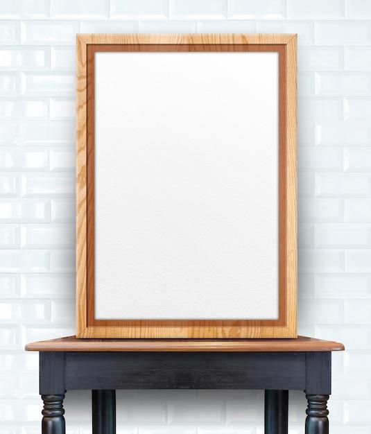 Leerer hölzerner fotorahmen, der an der weißen glatten fliesenwand auf weinleseholztabelle sich lehnt Premium Fotos