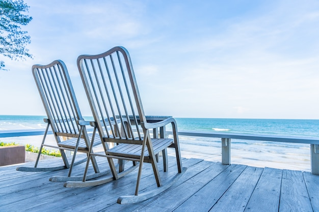 Leerer hölzerner stuhl und tabelle am patio am im freien mit schönem tropischem strand und meer Kostenlose Fotos