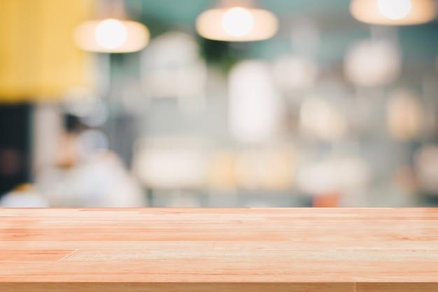 Leerer hölzerner tischplatte-aufnahmezähler oder bargeld-zähler auf unscharfem hintergrund für das montageprodukt vorhanden Premium Fotos