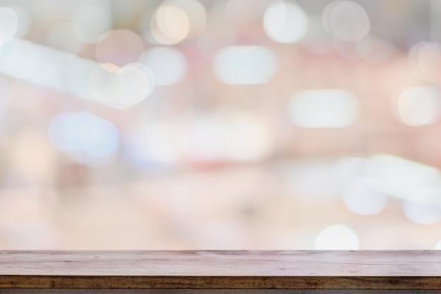 Leerer hölzerner tischplatte-zähler auf hellem bokeh innenraum verwischte hintergrund Premium Fotos