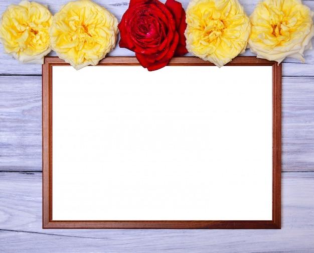 Leerer holzrahmen auf einem weißen hölzernen hintergrund, an der spitze der knospen von blühenden rosen Premium Fotos