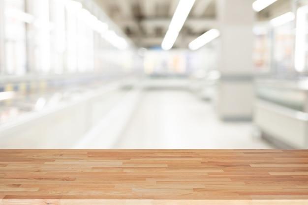 Leerer holztisch und innenhintergrund, produktanzeige, unscharfer heller innenhintergrund mit dem bokeh kaufhaus, bereiten für produktmontage vor. Premium Fotos