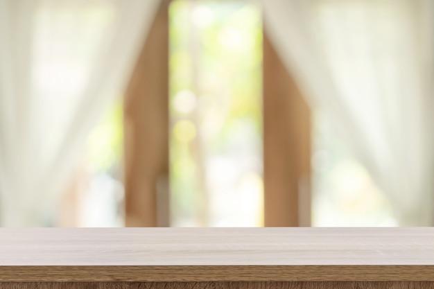 Leerer holztisch- und unschärfefensterhintergrund mit kopienraum, anzeigenmontage für produkt. Premium Fotos