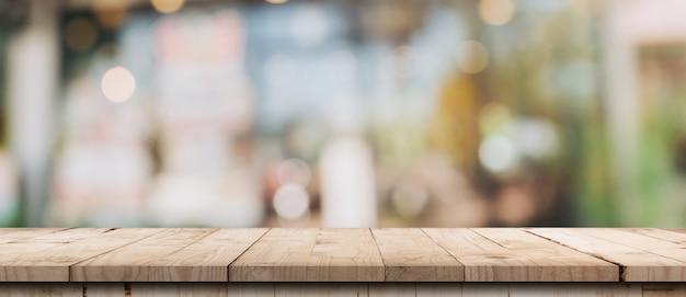 Leerer holztisch und unscharfer leuchttisch im café und im café mit bokeh-hintergrund. produktanzeigevorlage. Premium Fotos