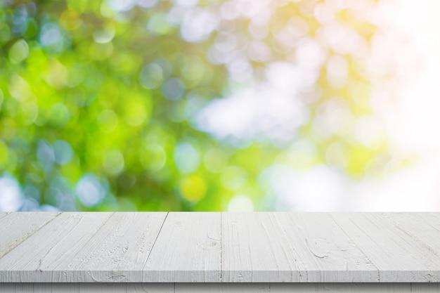 Leerer holztisch und zusammenfassung unscharfes grünes bokeh lässt hintergrundbeschaffenheit, anzeigenmontage mit kopienraum. Premium Fotos