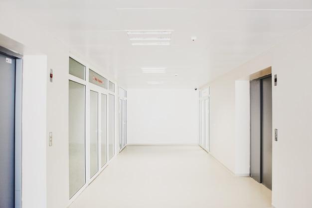 Leerer krankenhauskorridor mit glastüren Kostenlose Fotos