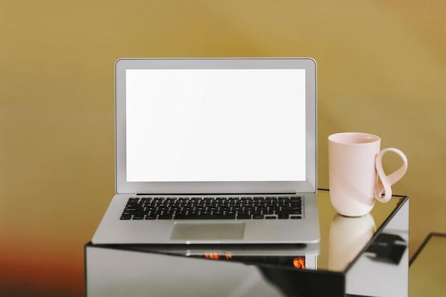 Leerer laptopbildschirm und eine rosa kaffeetasse Kostenlose Fotos