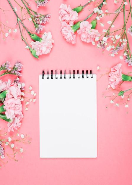 Leerer notizblock mit nelken verziert; gypsophila; limonium blumen auf rosa hintergrund Kostenlose Fotos